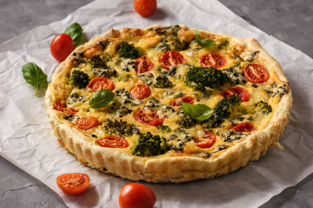 Homemade tart with broccoli, tomatoes and blue cheese. stock photo