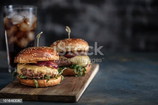 istock Homemade tasty hamburger with beef, cheese and caramelized onions. Street food, fast food. Copyspace 1016463082