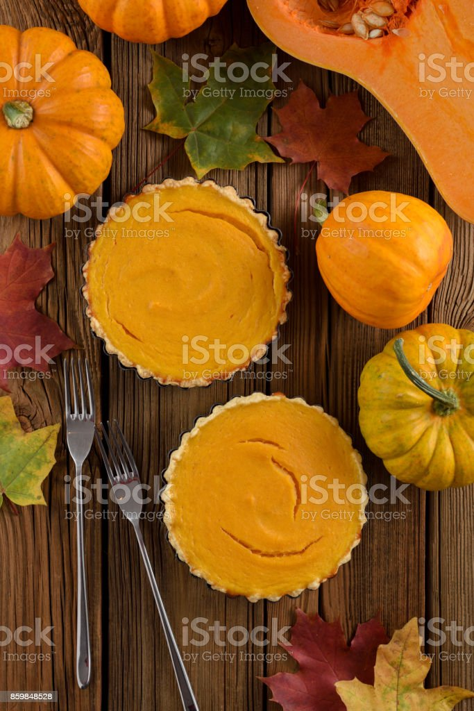 Homemade Thanksgiving dessert. Open pumpkin pies decorated with bright orange pumpkins and marple leaves on old wooden table stock photo