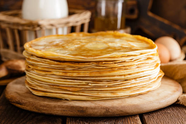 Homemade thin crepes with honey, pancakes on wooden rustic background stock photo