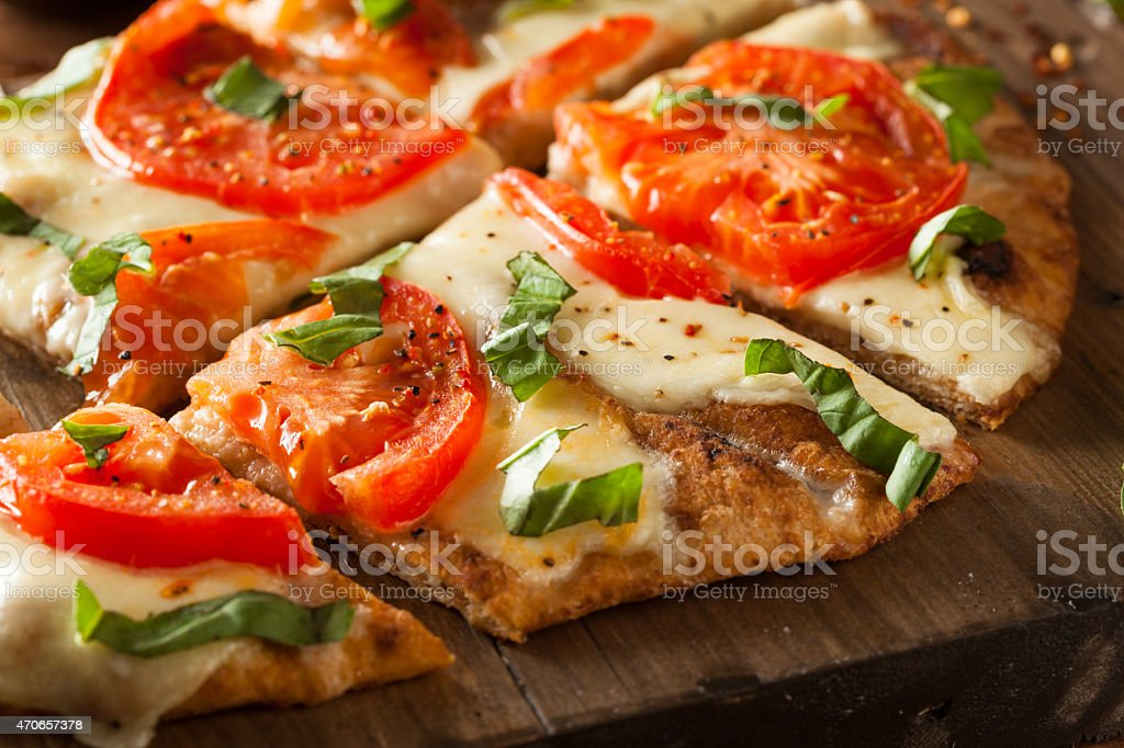 Homemade thin crust pizza with tomato topping stock photo