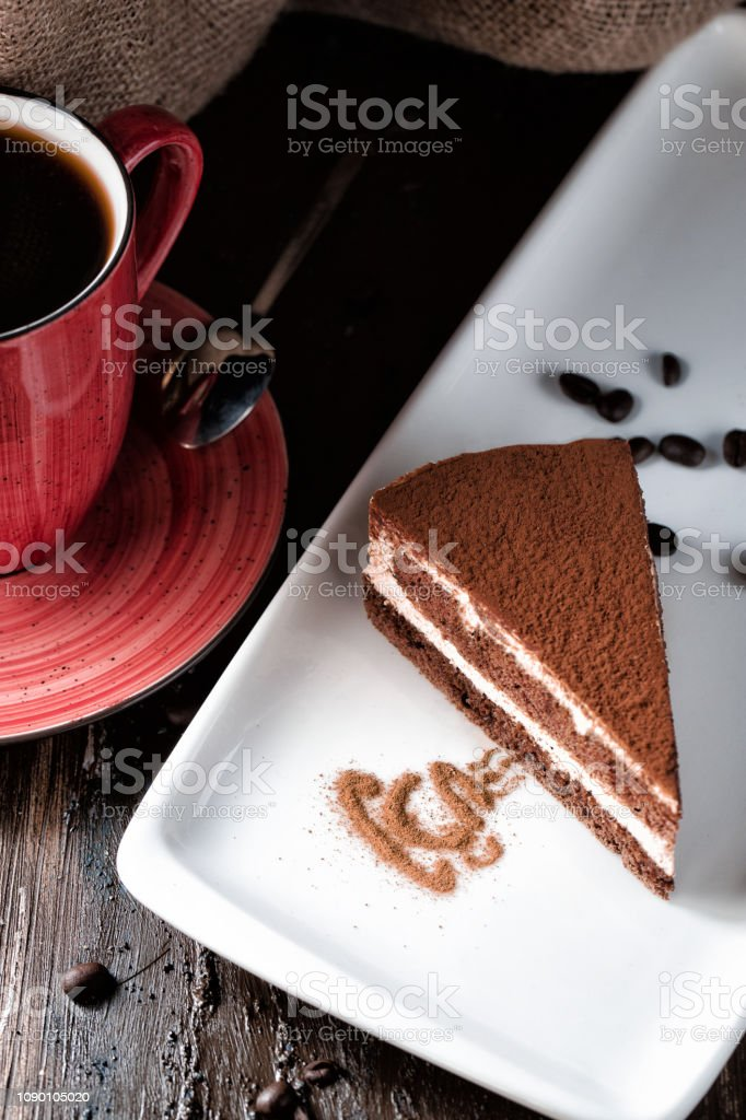 Tiramisu slice on white porcelain plate. Dark coffee in red mug....