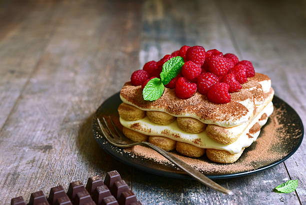 homemade tiramisu with raspberry on a black plate. - himbeer mascarpone dessert stock-fotos und bilder