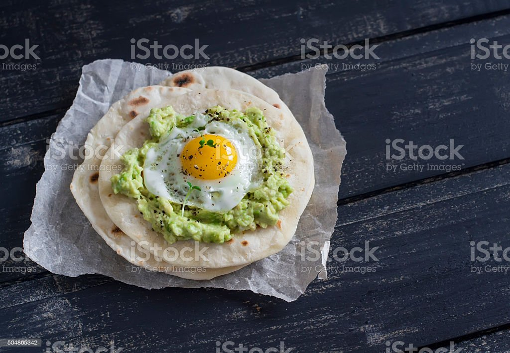 Homemade tortilla with mashed avocado and a fried quail egg. stock photo