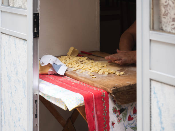 Homemade traditional pasta on a wooden board Homemade traditional pasta (orecchiette) on a wooden board. Bari, Italy. Tasty food concept orecchiette stock pictures, royalty-free photos & images