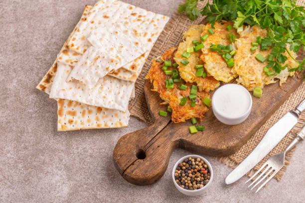 zelfgemaakte traditionele aardappel pannenkoeken hanukkah feest eten met knapperige matze op vintage snijplank - zout smaakstof stockfoto's en -beelden