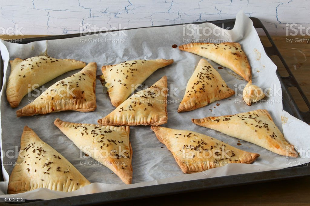 Homemade triangle pies on oven-tray stock photo