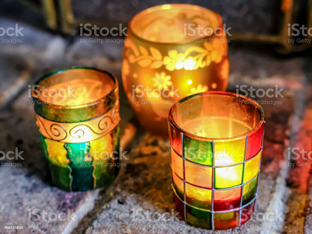 Home-made trio of glass coloured tea light jars seen by an open fireplace. stock photo