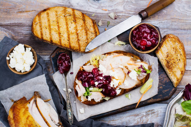 Homemade turkey leftover sandwich with cranberry sauce Homemade leftover thanksgiving day sandwich with turkey, cranberry sauce, feta cheese and vegetables. Top view leftovers stock pictures, royalty-free photos & images