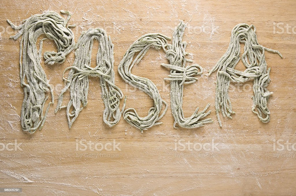 Homemade uncooked fresh green spaghetti forming the word PASTA royalty free stockfoto