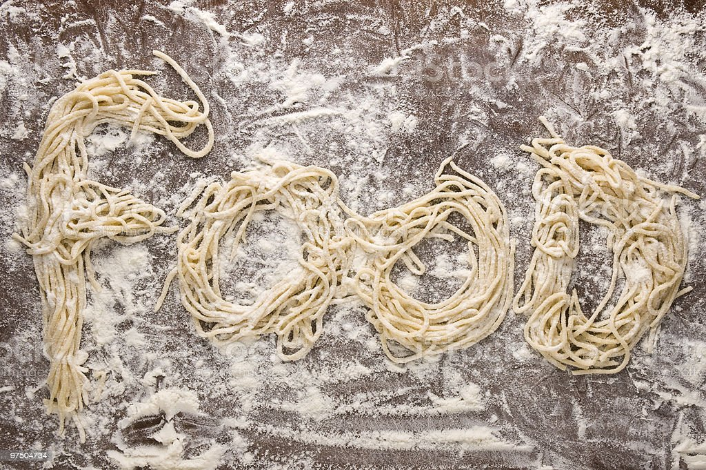 Home-made uncooked fresh spaghetti forming the word FOOD royalty-free stock photo