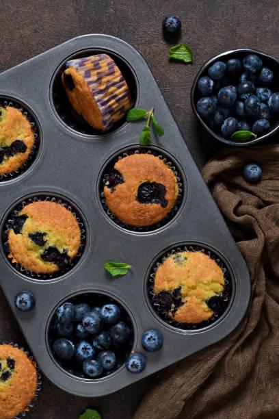 hausgemachte vanille muffins mit heidelbeeren auf einem dunklen hintergrund konkreter. rustikale! - vanille muffins stock-fotos und bilder
