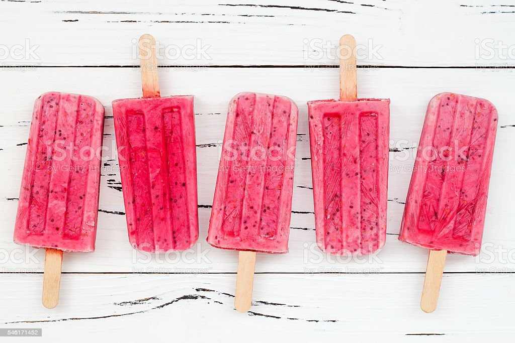 Homemade vegan raspberry coconut milk popsicles  with chia seeds stock photo