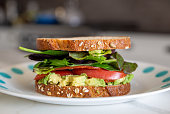 Homemade vegan sandwich with avocado, tomato, greens and vegan bacon