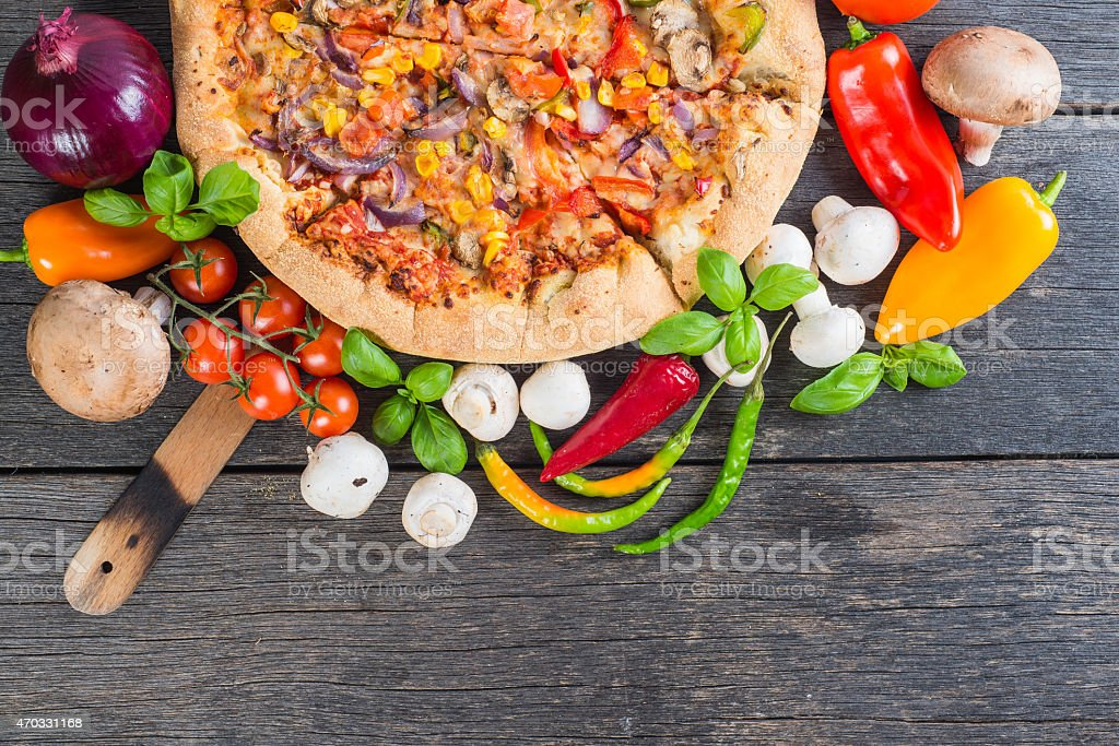 Homemade vegeterian pizza from above on wooden table stock photo