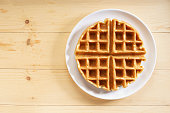 fresh baked waffle in a pattern on wooden background, top view