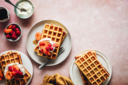Top view of plate of homemade waffle served with strawberry and raspberry. Preparing homemade waffle breakfast.