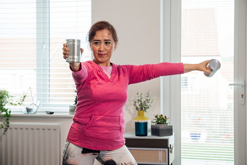 Senior woman standing in the living room of her home doing weight training with cans. She is in the North East of England.