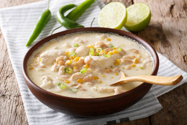 homemade white chili chicken with beans, lime and corn close-up. horizontal - chilli stock photos and pictures