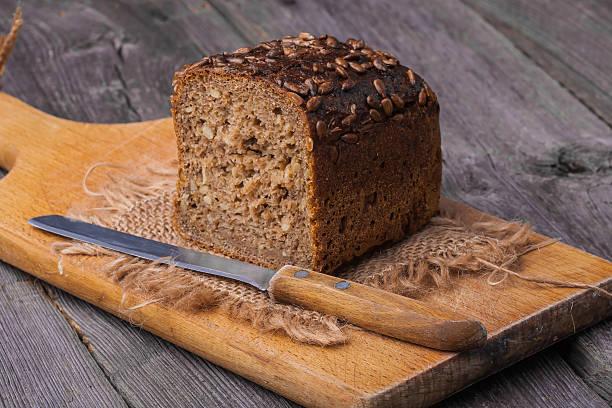 wholemeal pan casero en mesa de madera con cuchilla - pan multicereales fotografías e imágenes de stock