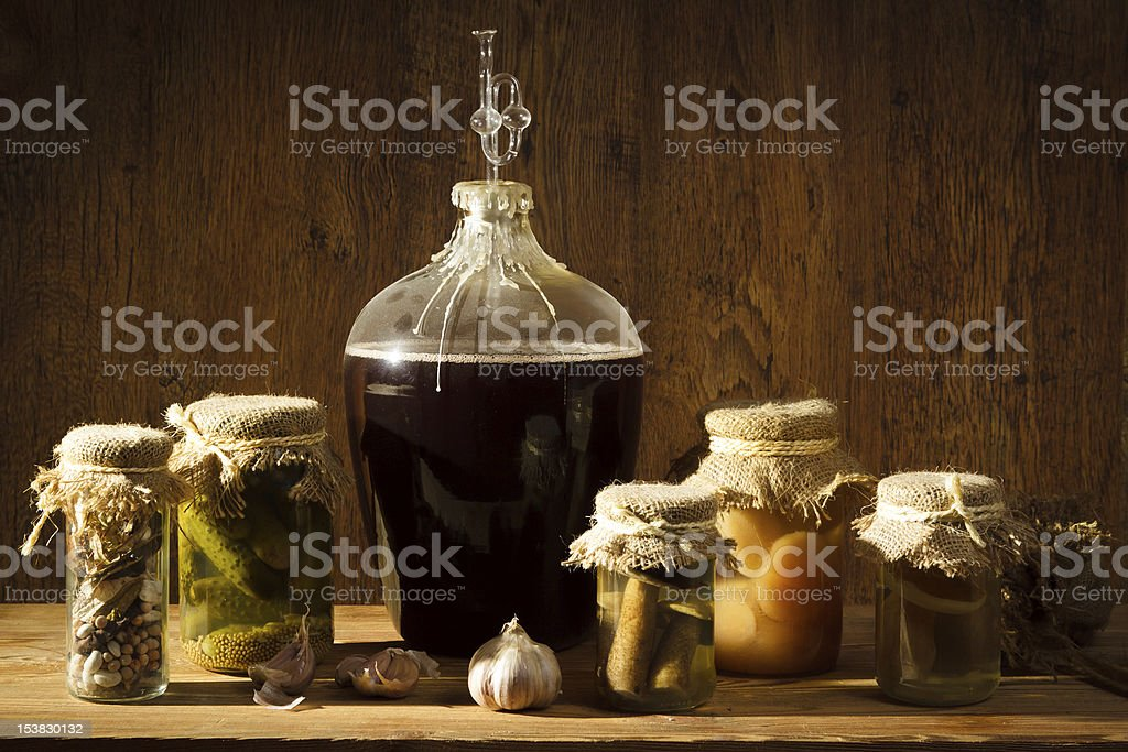 Homemade wine in larder with vegetables jars royalty-free stock photo