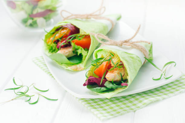 Homemade wrap sandwiches with basilic, chicken, vegetables and spinach sprouts stock photo