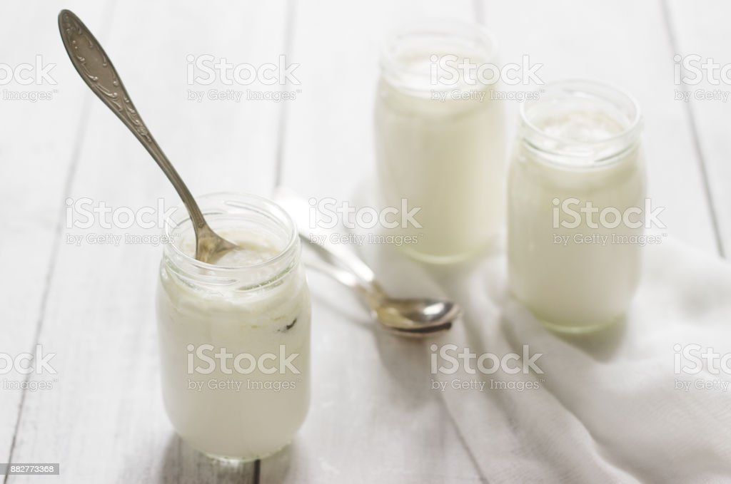 Homemade yogurt in a glass jar on a wooden table. Rustic style, selective focus. stock photo