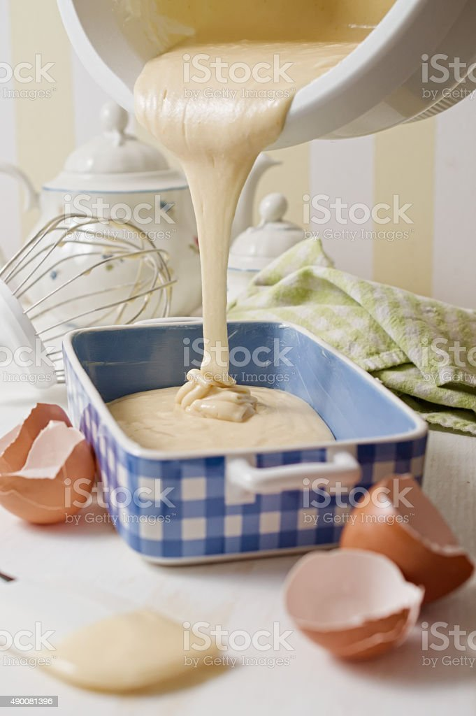Homemade yogurt sponge cake batter poured in blue ceramic dish stock photo