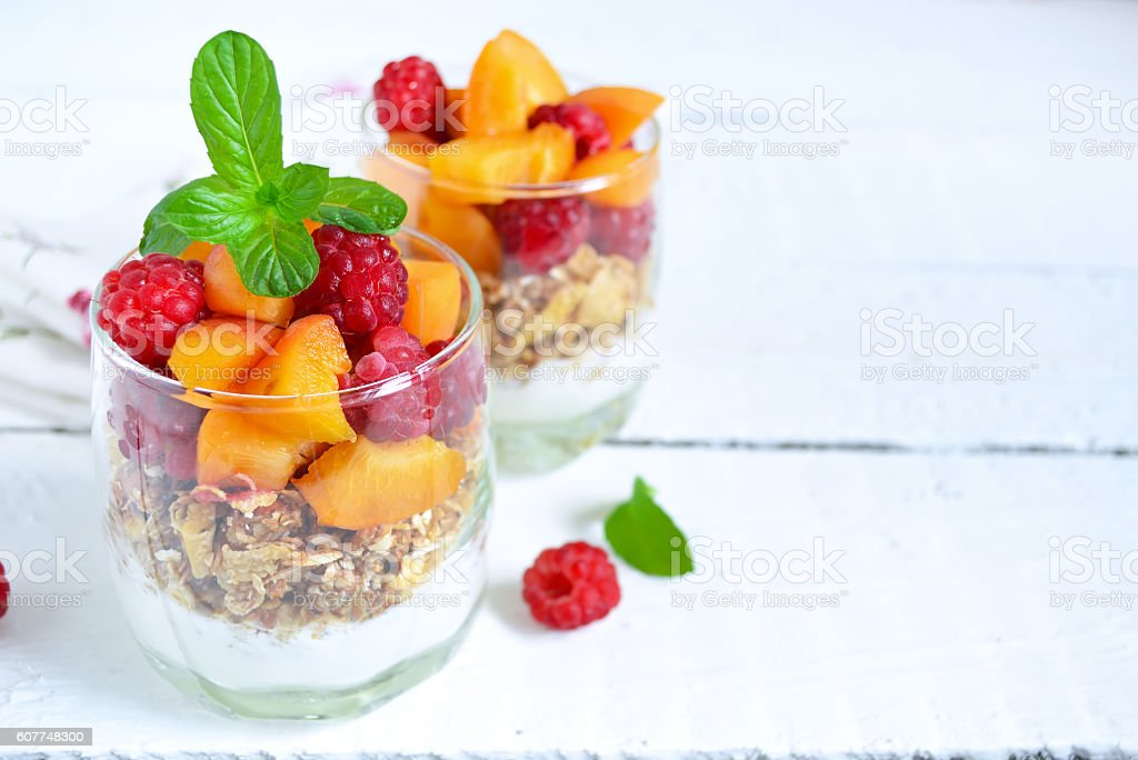 Homemade yogurt with granola apricots, peaches and raspberries o stock photo