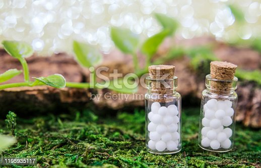 Homeopathic globule jelly beans in glass bottles close-up on a natural background. Selective focus. The concept of alternative medicine, banner, postcard. Copy space