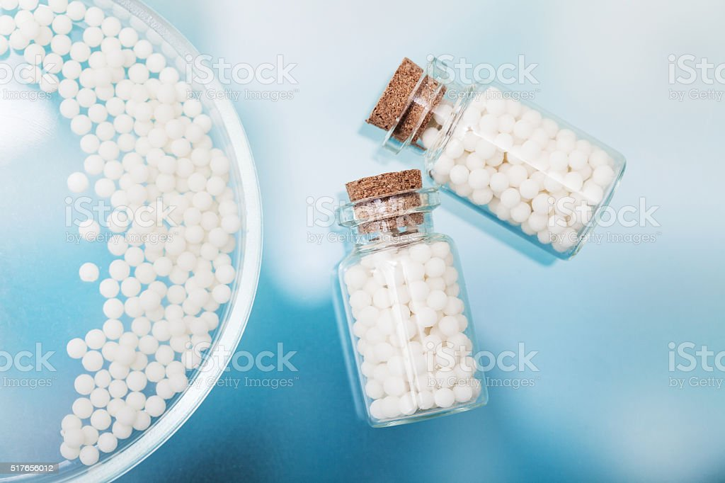 homeopathic pills lying on petri dish in a laboratory stock photo