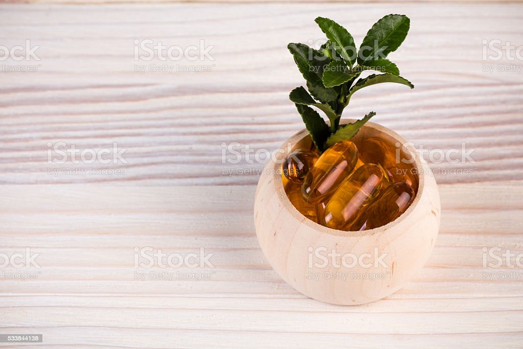 Homeopathic pills with green leaves stock photo