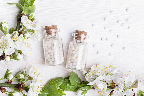 homeopathic pills with spring flowers on white wooden background stock photo