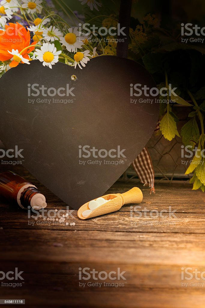 Homeopathy, globules with herbs stock photo