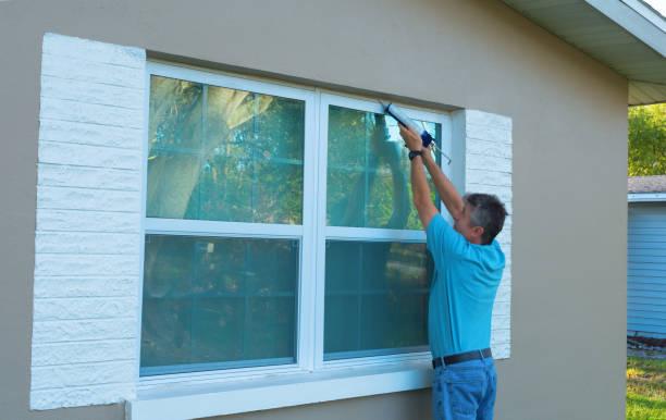 Homeowner caulking window weatherproofing home against rain and storms stock photo