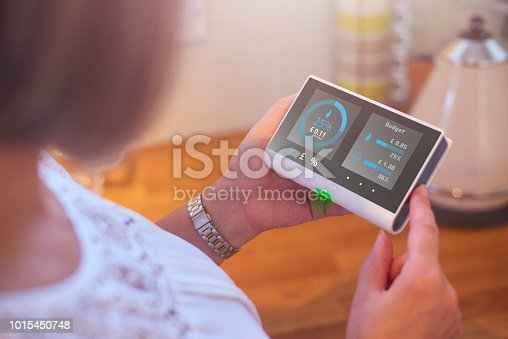 Homeowner checking current energy costs on smart meter in the kitchen of her home