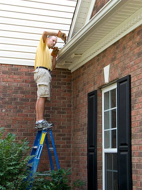 Homeowner Maintenance, Gutter Cleaning Working. Dangerously Standing On Ladder stock photo