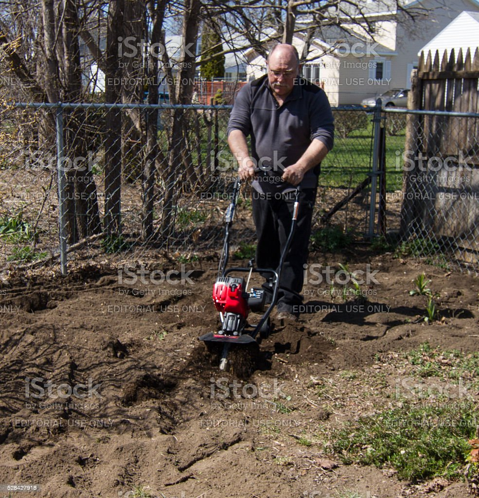 Homeowner prepares land for planting with small roto tiller stock photo