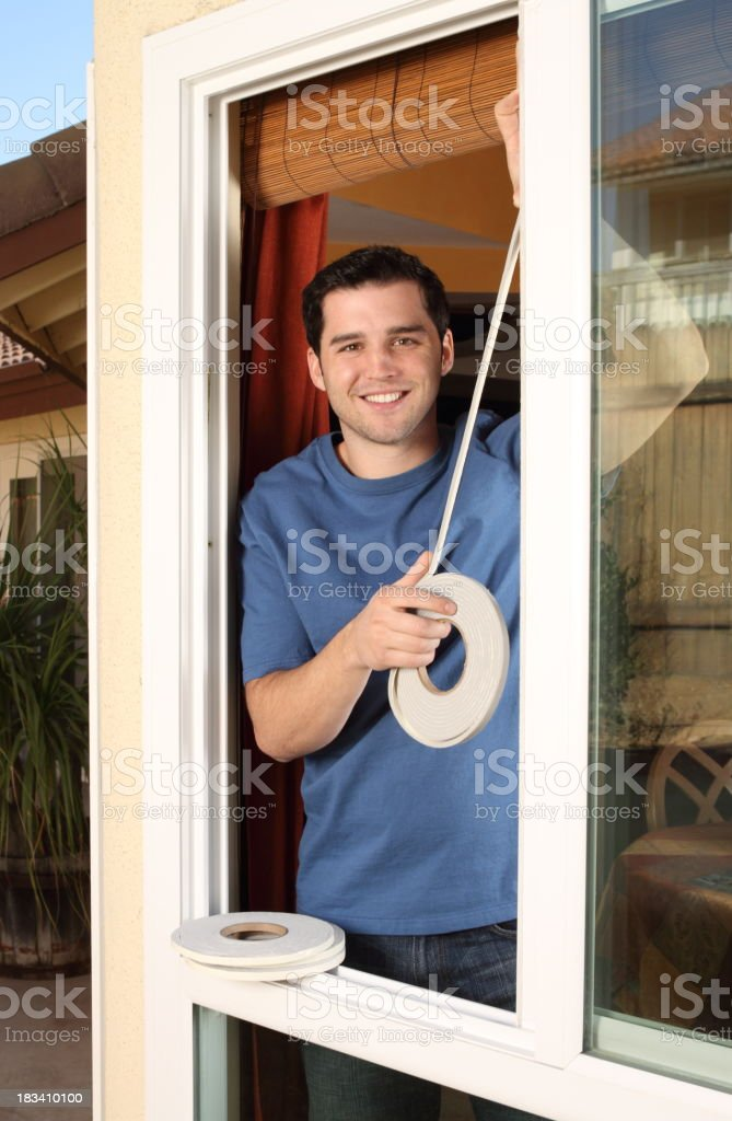 Homeowner Smiles While Installing Weather Stripping in Window stock photo
