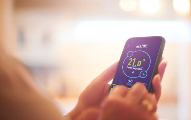 Homeowner using heating app Smart Home heating controls app smart thermostat stock pictures, royalty-free photos & images