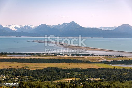 An elevated view of the Homer Spit and Kachemak Bay in Homer, Alaska during a summer day.