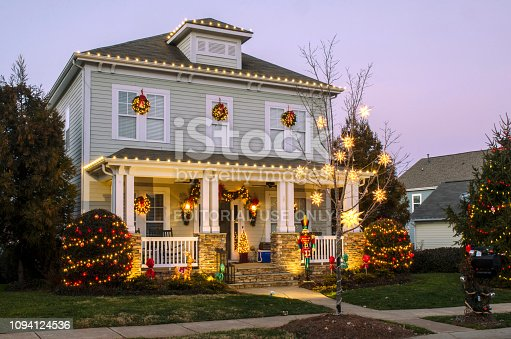 "McAdenville, North Carolina, USA - December 24, 2018: The quiet little town of McAdenville, which lies along the South Fork River in Gaston County N.C., comes alive in spectacular fashion each year as Christmas draws near. Almost overnight, the small textile town is transformed into ""Christmas Town, USA."" A tradition since 1956, Victorian-style, brick and wood sided homes are beautifully and tastefully decorated for the Holiday Season. Taken just before sunset to include a beautiful and colorful sky as a backdrop to this festive image."