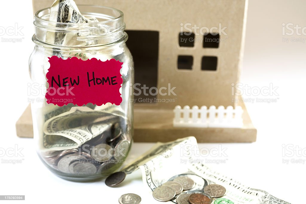 Homes:  Money Jar with US currency.  Saving for New Home royalty-free stock photo
