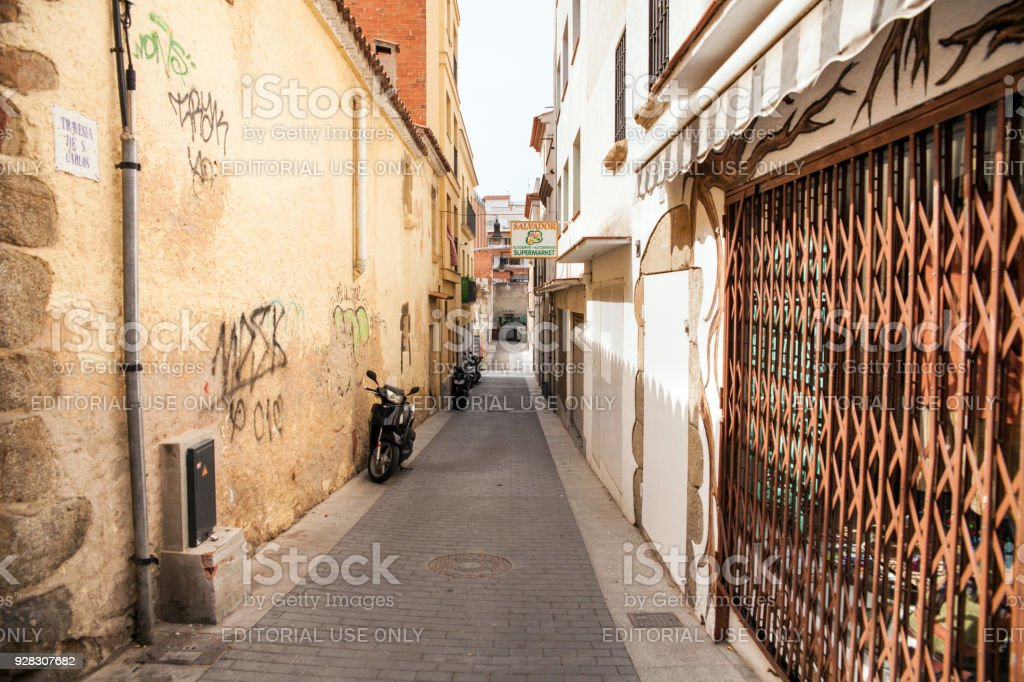Homes near the narrow streets of Lloret de Mar. Downtown of Lloret, Spain. Tourists walking the streets of the city. stock photo