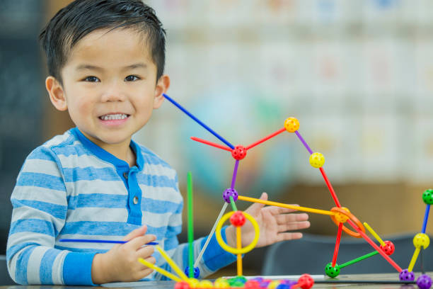 Homeschool Games A young east Asian boy wearing a striped sweater is playing with educational toys in an indoor, homeschool environment. preschool student stock pictures, royalty-free photos & images
