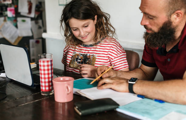 Homeschooling and working, family at home working side by side stock photo