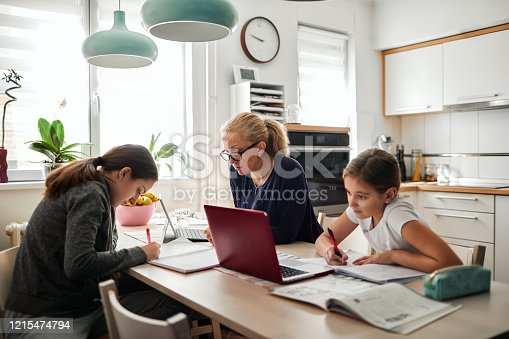 Mother helping her daughters to finish school homework during coronavirus quarantine. They are using laptop.