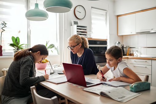 Mother helping her daughters to finish school homework during coronavirus quarantine. They are using laptop.