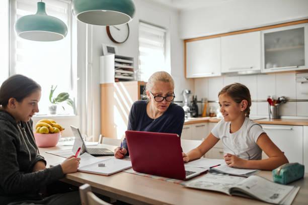 Homeschooling - Mother Helping To Her Daughters To Finish School Homework During Coronavirus Quarantine stock photo