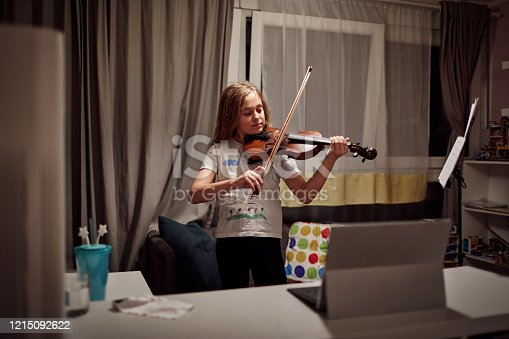 Cute girl playing violin on online class during coronavirus quarantine.